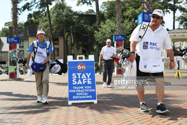 Caddies walk past signage promoting social distancing as a COVID-19 precaution during the second round of the RBC Heritage on June 19, 2020 at...