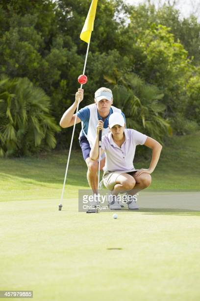 Carro y golfista preparando para putt