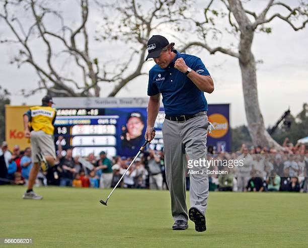 """Caddy Jim """"Bones"""" MacKay, left, celebrates with Phil Mickelson after sinking a putt on the 18th hole, winning the final round of the Northern Trust..."""