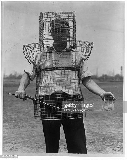 Caddy Mozart Johnson demonstrates mousetrap armor to protect caddies and ball retrievers from wild golf balls
