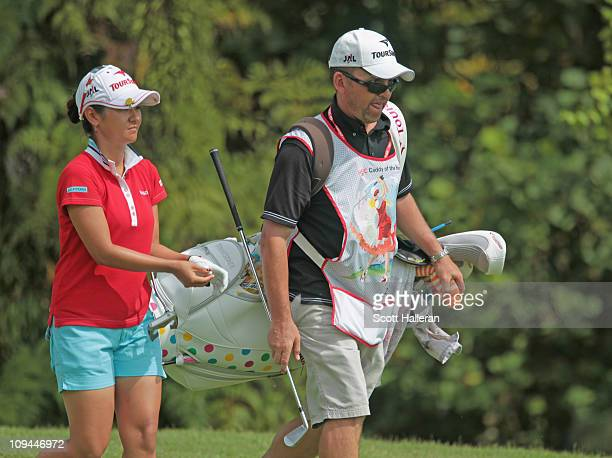 Caddy of the Year Mick Seaborn alongside player Ai Miyazato of Japan during the third round of the HSBC Women's Champions 2011 at the Tanah Merah...