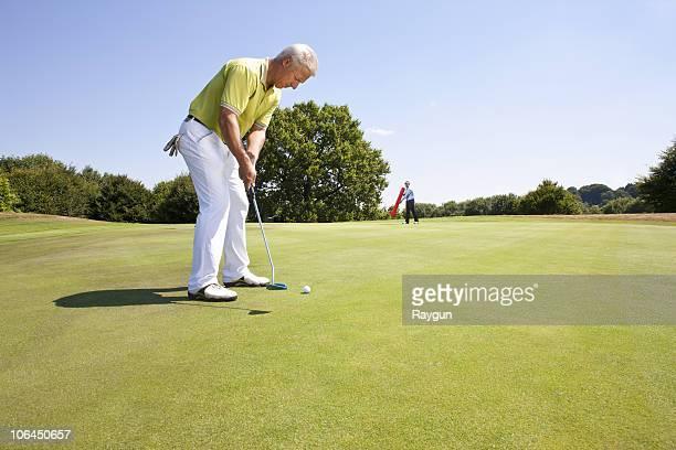 caddy pointing at a hole on golf course - einlochen golf stock-fotos und bilder