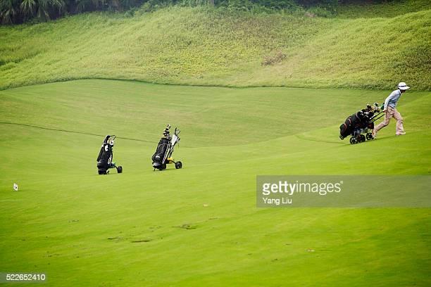 Caddy Pulling Golf Clubs