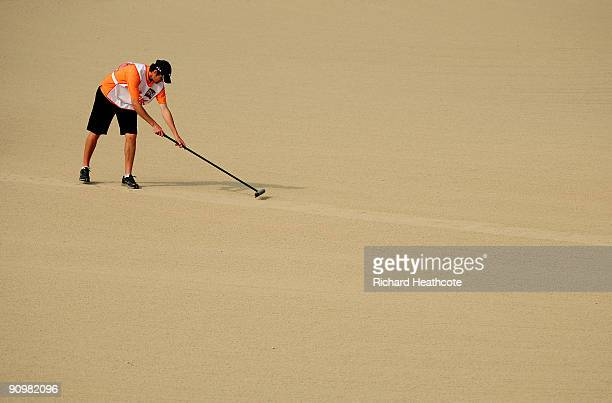 A caddy rakes a fairway bunker during the fourth round of the Austrian Golf Open at Fontana Golf Club on September 20 2009 in Vienna Austria