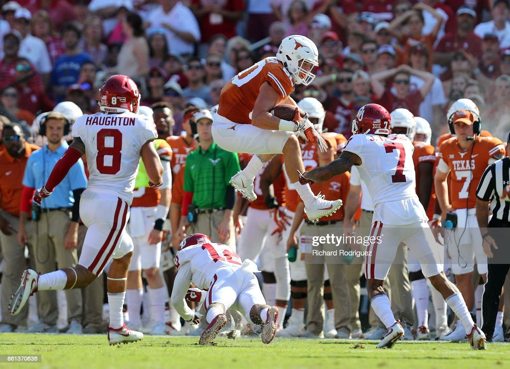 Cade Brewer #80 of the Texas Longhorns leaps over Will Johnson #12 of the Oklahoma Sooners in the second quarter at Cotton Bowl on October 14, 2017 in Dallas, Texas.