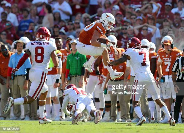 Cade Brewer of the Texas Longhorns leaps over Will Johnson of the Oklahoma Sooners in the second quarter at Cotton Bowl on October 14, 2017 in...