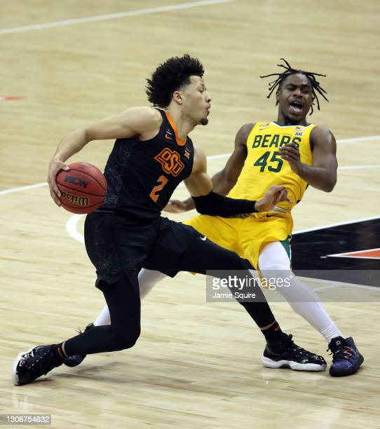 Cade Cunningham of the Oklahoma State Cowboys commits a player control foul as he knocks down Davion Mitchell of the Baylor Bears during the Big 12...