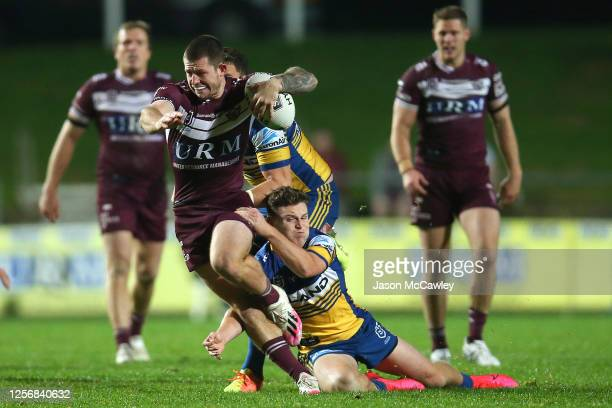 Cade Cust of the Sea Eagles is tackled by Brad Takairangi of the Eels during the round 10 NRL match between the Manly Sea Eagles and the Parramatta...