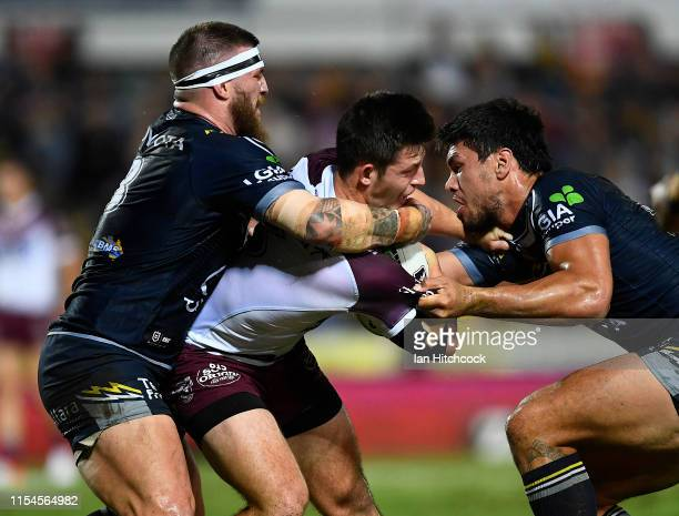 Cade Cust of the Sea Eagles is tackled by Josh McGuire and Jordan McLean of the Cowboys during the round 13 NRL match between the North Queensland...