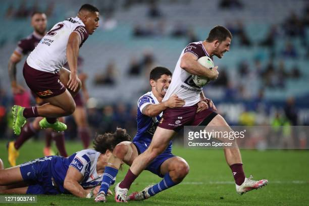 Cade Cust of the Sea Eagles is tackled during the round 18 NRL match between the Canterbury Bulldogs and the Manly Sea Eagles at ANZ Stadium on...