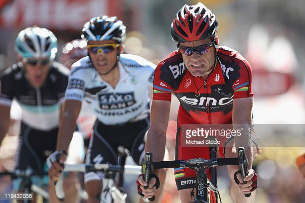 Cadel Evans of Australia and BMC Racing Team crosses the finishing line alongside Alberto Contador of Spain and Saxo Bank Sungard and Andy Schleck of...