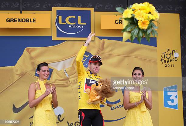 Cadel Evans of Australia and BMC Racing Team throws a bouquet of flowers into the crowd after becoming the race leaders yellow jersey after the...