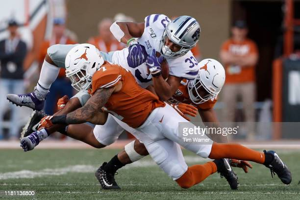 Caden Sterns of the Texas Longhorns and Ayodele Adeoye tackle Tyler Burns of the Kansas State Wildcats in the fourth quarter at Darrell K RoyalTexas...