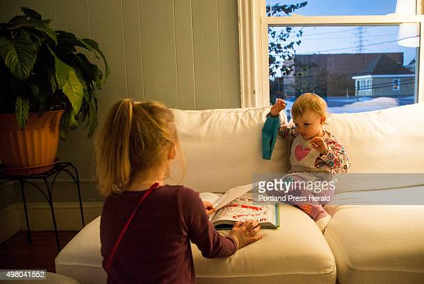 Cadence Kessler, left, reads a Dr. Seuss book with her sister Lyla in their living room in South Portland, ME on Monday, October 26, 2015.
