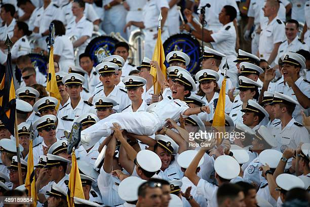 A cadet is tossed in the air after the Navy Midshipmen scored against East Carolina Pirates in the fourth quarter of their 4521 win on September 19...