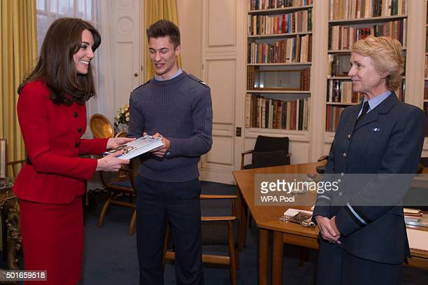 Cadet Sergeant Tommy Dade stands with the Duchess of Cambridge as she is presented with a book by Air Commodore Dawn McCafferty Commandant of the Air...