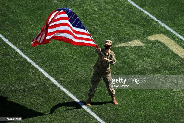 Cadet wearing a mask waves an American flag as the Army Black Knights take the field before their game against the Middle Tennessee Blue Raiders at...