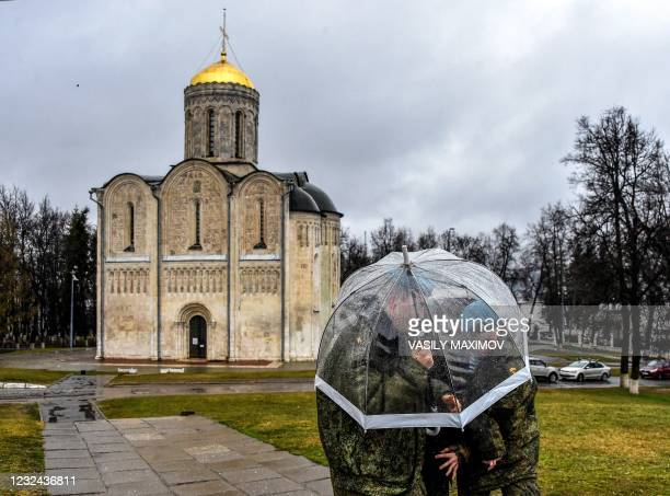 Cadets hide from the rain under an umbrella near a church in the town of Vladimir on April 21 where jailed Kremlin critic Alexei Navalny was...