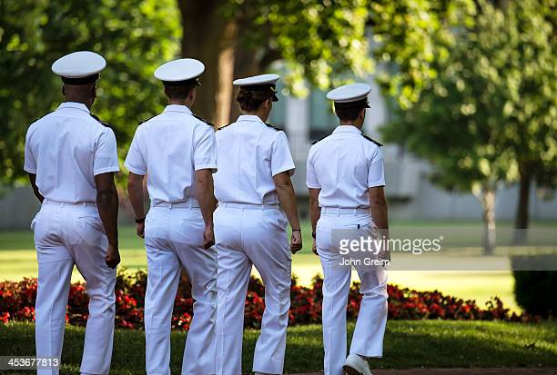 Cadets in sevice whites march on the campus of the US Naval Academy