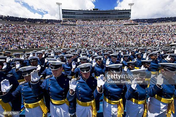Cadets raise their right hands as they take the oath of office to become 2nd Lieutenants during the graduation ceremony for the United States Air...