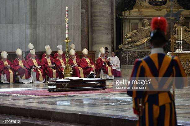 Cadinals sit in front of the coffin of Cardinal Roberto Tucci during his funeral at St Peter's basilica on April 17 2015 at the Vatican AFP PHOTO /...