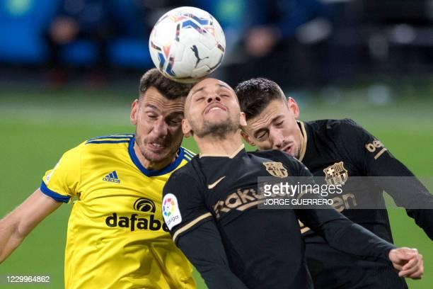 Cadiz' Swiss defender Jean-Pierre Rhyner vies with Barcelona's Danish forward Martin Braithwaite and French defender Clement Lenglet during the...