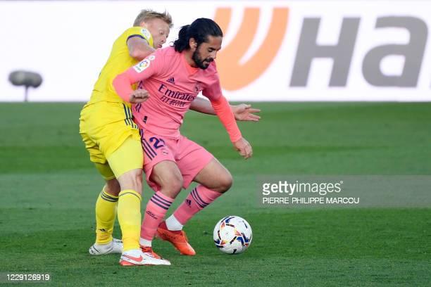 Cadiz's Danish midfielder Jens Jonsson vies with Real Madrid's Spanish midfielder Isco during the Spanish League football match between Real Madrid...