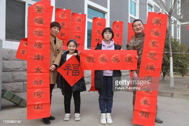 Cadre Liu Guanghui shows couplets written by his eldest daughter with his wife and daughter in Luoyang, Henan province, China, Feb 4, 2021.-...