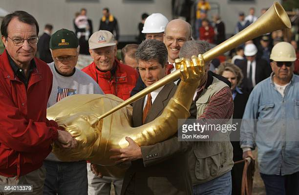 A cadre of church members of the Newport Beach Temple walk the golden figure of an angel to a waiting crane for placement atop the church's spire The...