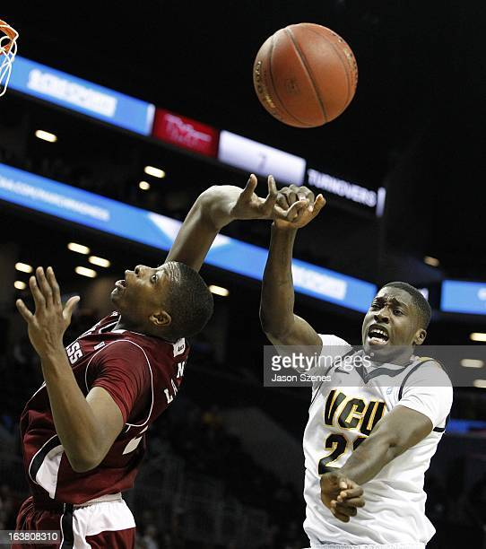 Cady Lalanne of the Massachusetts Minutemen and Jarred Guest of Virginia Commonweath Rams fight for a rebound during the first half during the...