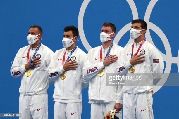 Caeleb Dressel, Blake Pieroni, Bowen Becker and Zach Apple of United States celebrates their gold medals in the Men's 4x100m freestyle relay on day...