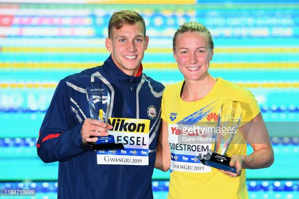 Caeleb Dressel of the United States and Sarah Sjostrom of Sweden pose with their respective trophies for best male and best female swimmers on day...