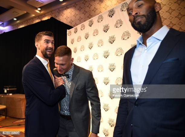 Caeleb Dressel winner of Male Athlete of the Year is congratulated by presenters Michael Phelps and Kobe Bryant during the 2017 USA Swimming Golden...