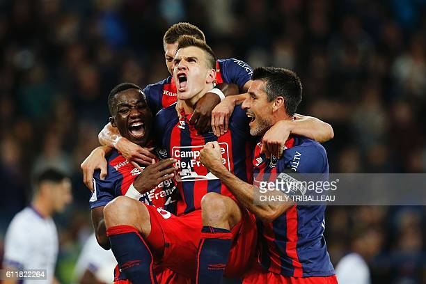 Caen's Croatian forward Ivan Santini celebrates with teammates after scoring during the French L1 football match between Caen and Toulouse on October...