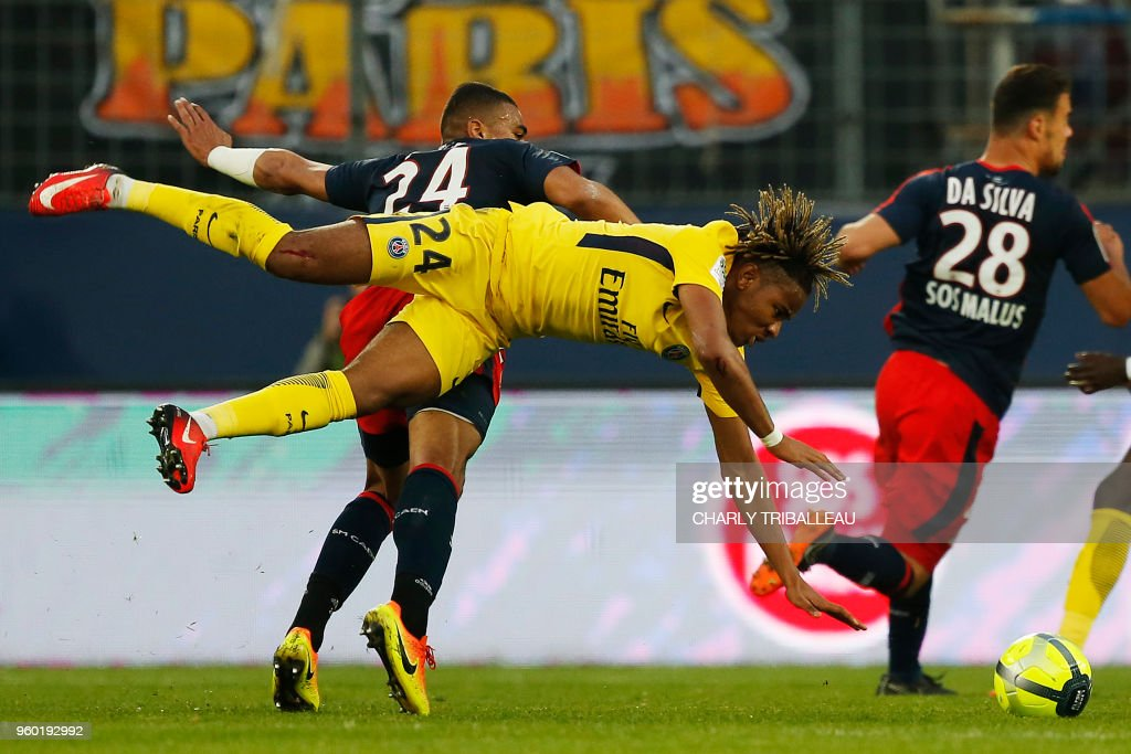TOPSHOT - Caen's French defender Alexander Djiku (L) vies for the ball with Paris Saint-Germain's midfielder Christopher Nkunku (R) during the French L1 football match between Caen (SMC) and Paris (PSG) on May 19, 2018, at the Michel d'Ornano stadium, in Caen, northwestern France.