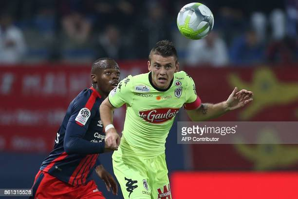 Caen's French forward Herve Bazile and Angers' French midfielder Pierrick Capelle eye the ball during the French L1 football match between Caen and...