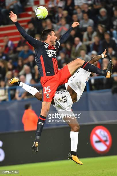Caen's French midfielder Julien Feret and Amiens' Congolese midfielder Gael Kakuta go for a header during the French L1 football match between Caen...
