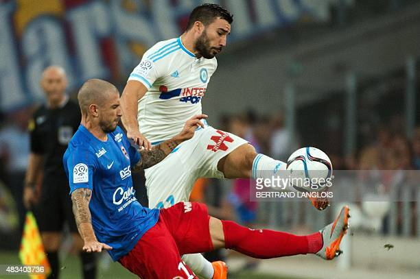 Caen's French midfielder Vincent Bessat vies with Marseille's French midfielder Romain Alessandrini during the French L1 football match between...