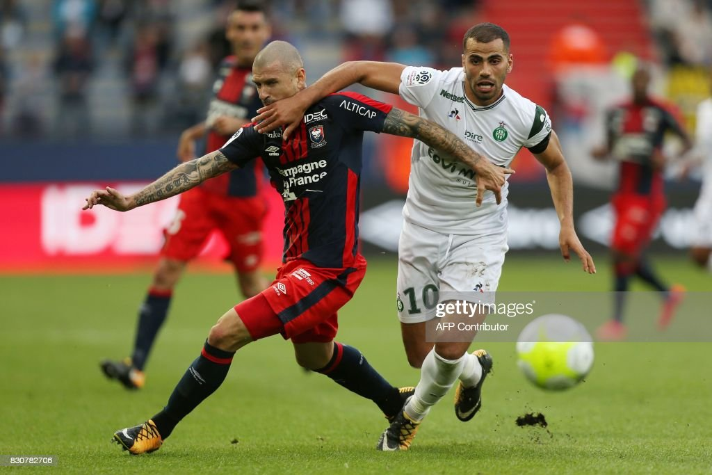 Caen's French midfielder Vincent Bessat (L) vies with Saint-Etienne's French forward Oussama Tannane (R) during the French L1 football match between Caen (SMC) and Saint-Etienne (ASSE) on August 12, 2017, at the Michel d'Ornano stadium, in Caen, northwestern France. /