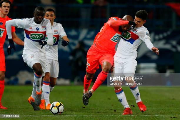 Caen's FrenchGuinean midfielder Baissama Sankoh vies for the ball with Lyon's forward Houssem Aouar and Lyon's defender Mouctar Diakhaby during the...