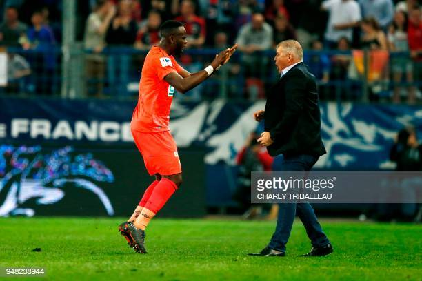 Caen's Ivorian midfielder Ismael Diomande reacts after scoring with Caen's French head coach Patrice Garande during the French cup semifinal match...