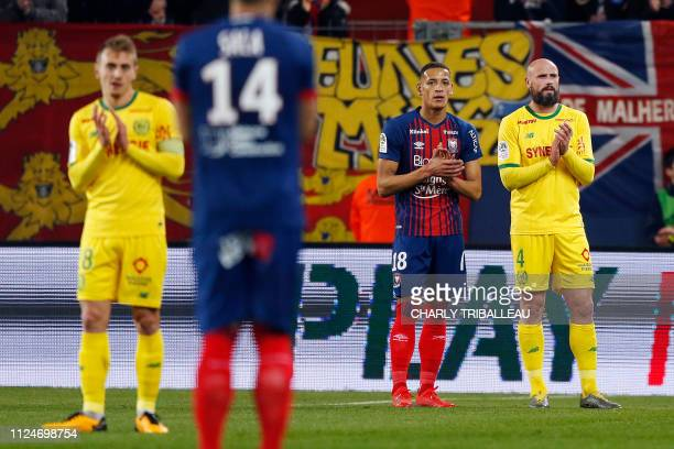 Caen's Moroccan forward Yacine Bammou Nantes' French defender Nicolas Pallois applaud along with their teammates in tribute to Argentine footballer...