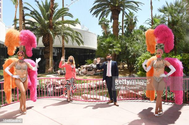 Caesars Entertainment Regional President Eileen Moore and GM of Flamingo Las Vegas Ken Janssen pose for photos with two showgirls at the reopening of...