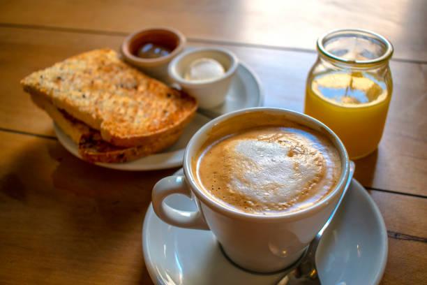Café con leche y tostadas de campo con queso crema y mermelada, y jugo exprimido de naranja