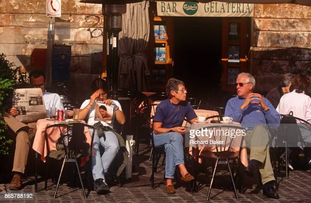 Cafe couple read a copy of Correre della Sera newspaper and a womens' magazine in the Italian capital, on 3rd November 1999, in Rome, Italy.