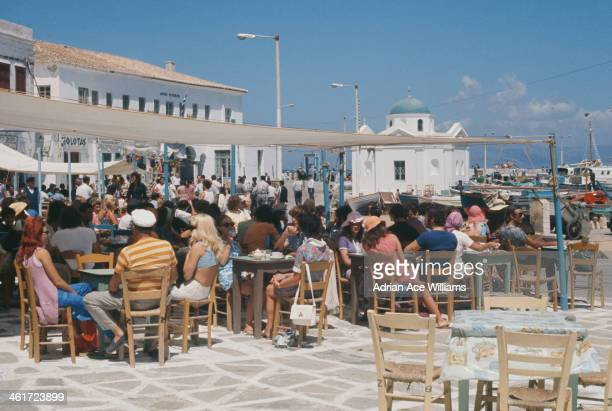 A cafe in Chora harbour on the island of Mykonos Greece circa 1970 Visible behind is the little church of Agios Nikolaos