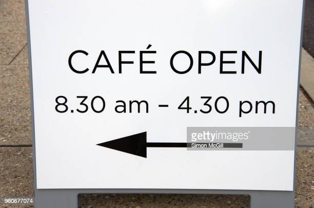 'Cafe Open' sandwich board sign on a sidewalk