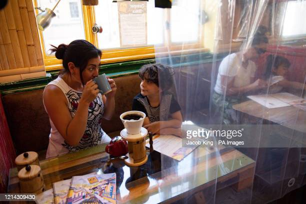 Cafe owner Francini Osorio serves customers in a trial phase during the coronavirus lockdown Osorio has installed an air purifier and 35 clear shower...