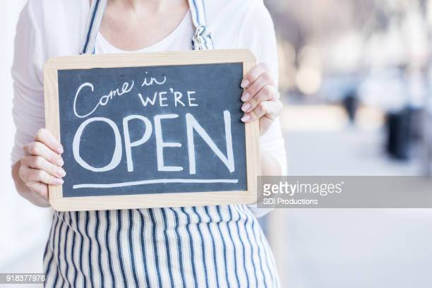 cafe owner holding 'open' sign outdoors - open for business stock pictures, royalty-free photos & images