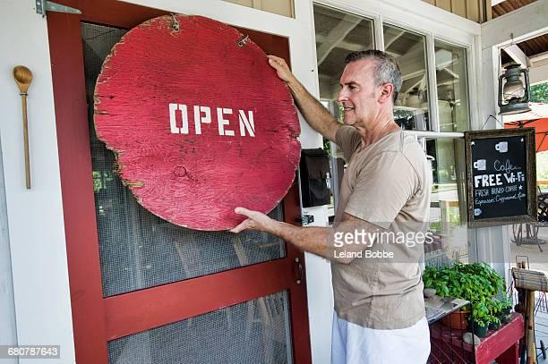 Cafe owner putting up signage on front door